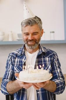 Mann mit partyhut hält einen kuchen mit kerzen. mann trägt hemd.