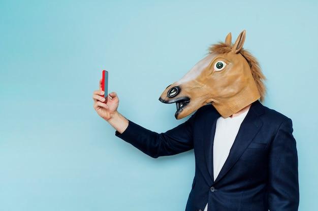 Mann mit pferdemaske macht ein selfiegeschäftsmann mit pferdemaske macht ein selfie