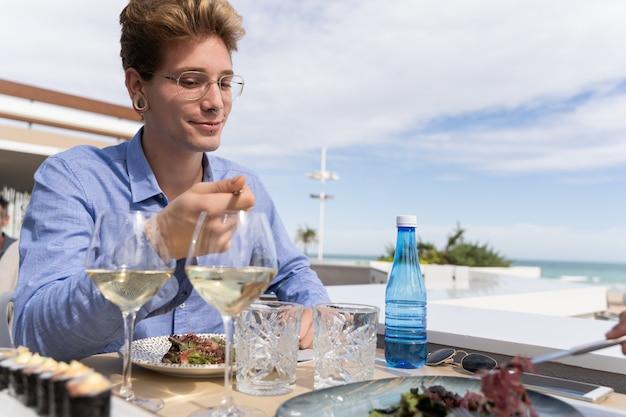 Mann mit piercings, die in einem restaurant mit zwei gläsern weißwein mit shushi essen essen