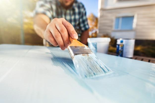 Mann mit pinsel in der hand und malerei auf dem holzbrett
