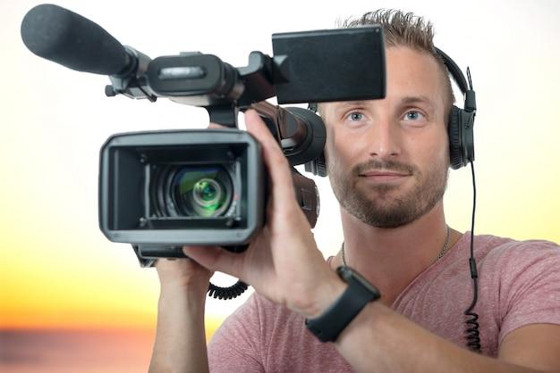Mann mit professionellem camcorder und kopfhörern