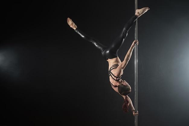 Mann mit pylon. männlicher stangentänzer, der auf einem schwarzen hintergrund tanzt