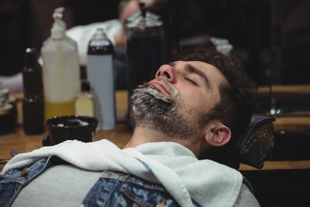 Mann mit rasierschaum auf bart, der auf stuhl entspannt
