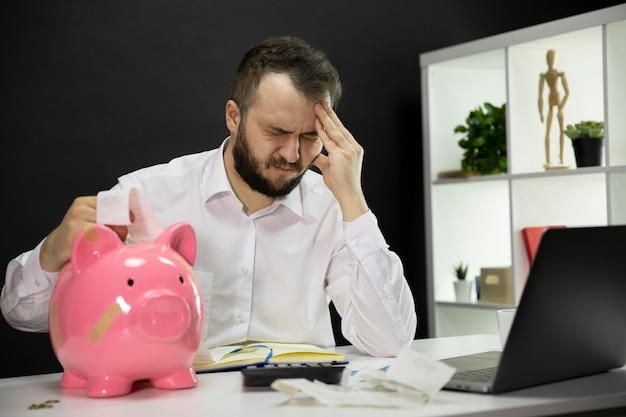 Mann mit rechnungen und kaputtem sparschwein auf dem schreibtisch machte sich sorgen um finanzielle probleme