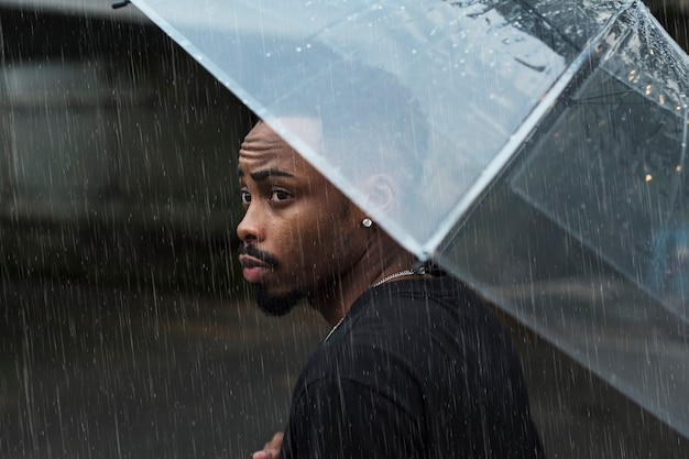 Mann mit regenschirm an einem regnerischen tag