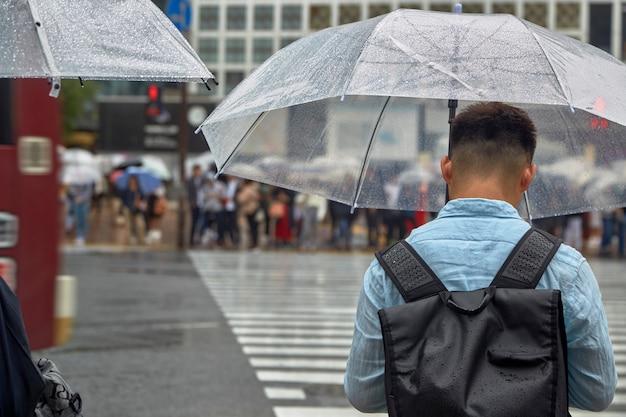 Mann mit regenschirm gehen