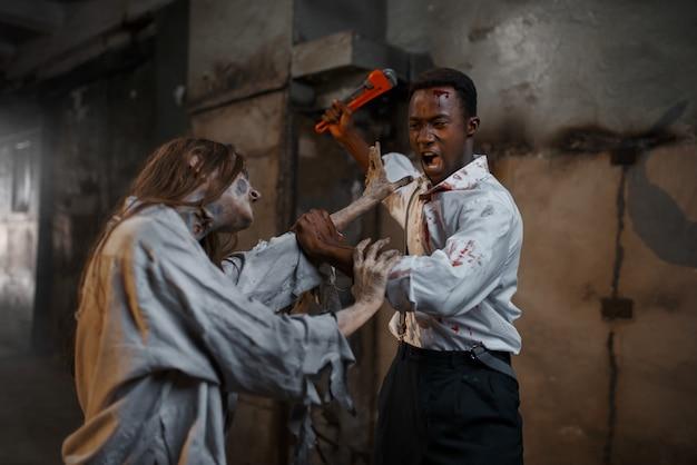 Mann mit rohrzange tötet weiblichen zombie, tödliche jagd. horror in der stadt, gruseliger krabbeltierangriff, weltuntergangsapokalypse, gruseliges blutiges monster