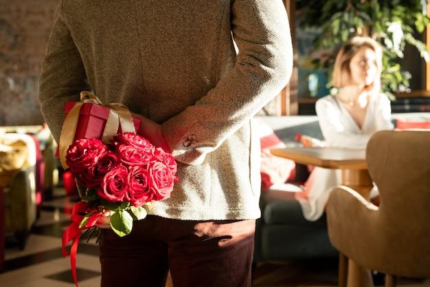 Mann mit rosen und geschenkbox