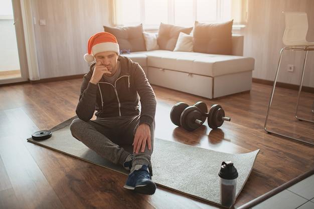 Mann mit rotem hut auf dem kopf sitzt auf matte