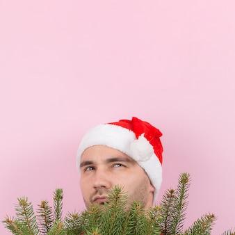 Mann mit rotem hut schaut hinter den weihnachtsbäumen hervor