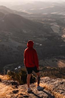 Mann mit rotem sweatshirt mit unscharfer landschaft