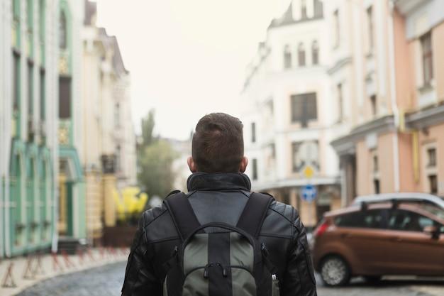 Mann mit rucksack auf alter straße
