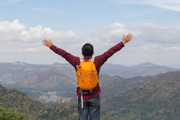 Mann mit rucksack auf eine oberseite der felsen ower schönen schluchtflußlandschaft.