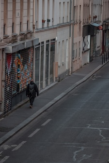 Mann mit rucksack, der auf bürgersteig geht