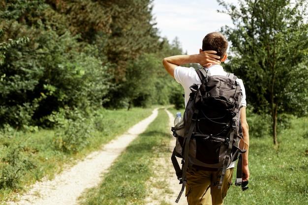 Mann mit rucksack, der natur erforscht