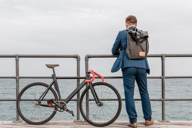 Mann mit rucksack, der neben seinem fahrrad steht