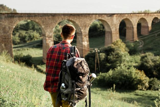 Mann mit rucksack im grünen feld