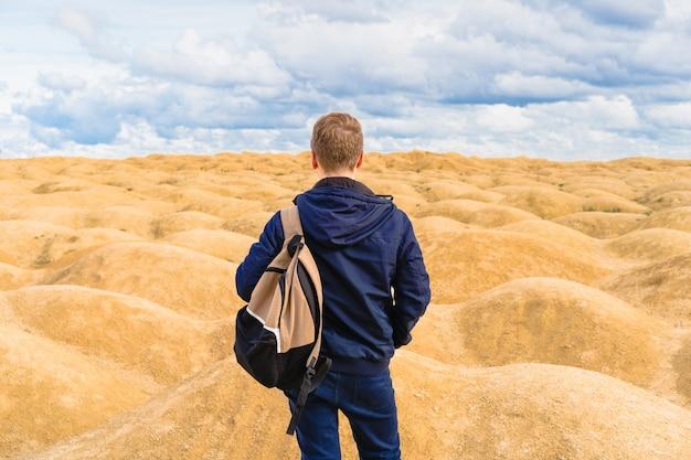 Mann mit rucksack steht in der wüste