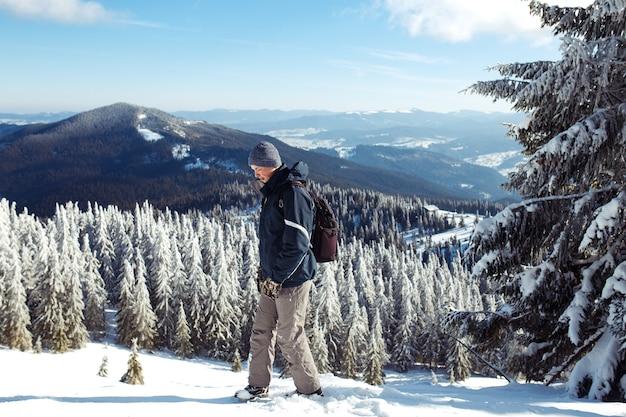 Mann mit rucksack trekking in den bergen. kaltes wetter, schnee auf hügeln. winterwandern. der winter kommt, erster schneefall. konzept von reisen, ruhe, entspannung