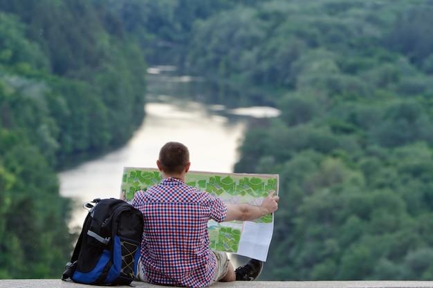 Mann mit rucksack und offener topografischer karte sitzt auf dem hintergrund des flusses und des grünen waldes