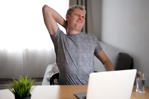 Mann mit rückenschmerzen sitzt im haus
