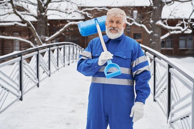 Mann mit schaufel auf schulter im winter