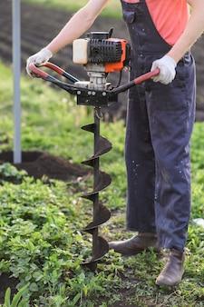 Mann mit schaufel gräbt den boden
