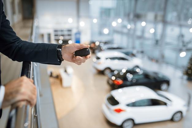 Mann mit schlüsseln von seinem neuen transport im autohaus. kunde im ausstellungsraum für neue fahrzeuge, männliche person, die automobil kauft, autohändlergeschäft