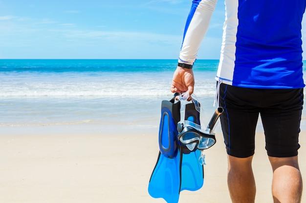 Mann mit schnorchelausrüstung in den händen, die zum meer auf strand gehen