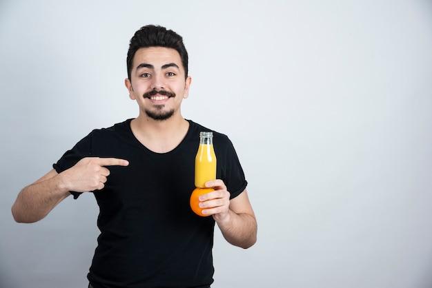 Mann mit schnurrbart, der auf orangenfrucht mit glasflasche saft zeigt.