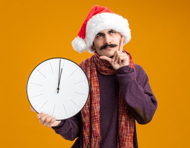 Mann mit schnurrbart, der eine weihnachtsmütze mit einem warmen schal um den hals trägt und eine uhr hält, die verwirrt über der orangefarbenen wand steht?