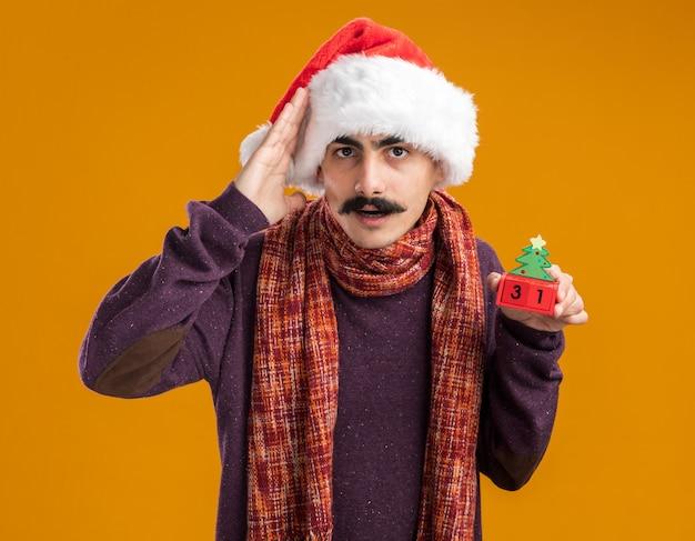 Mann mit schnurrbart, der weihnachtsweihnachtsmütze mit warmem schal um seinen hals trägt, der spielzeugwürfel mit datum fünfundzwanzig betrachtet kamera betrachtet, die mit hand über kopf verwechselt wird, der über orange hintergrund steht