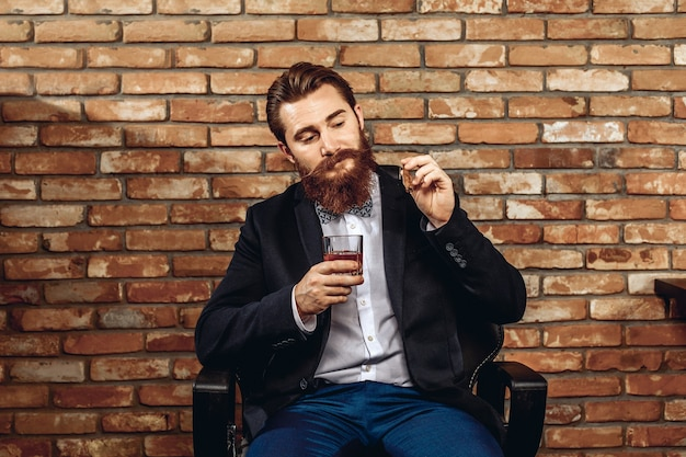 Mann mit schnurrbart und bart sitzt auf einem stuhl und hält ein glas whisky und eine zigarre in der hand und posiert