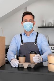 Mann mit schürze bereitet essen zum mitnehmen vor