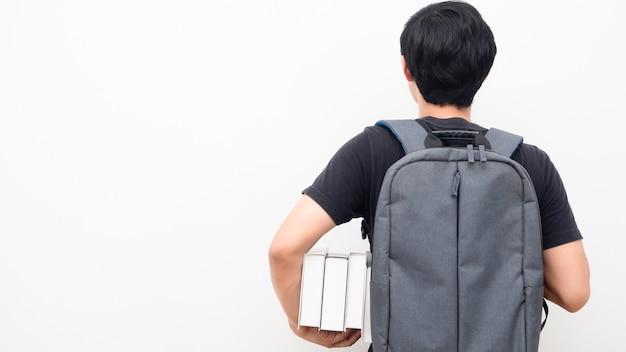 Mann mit schulrucksack und hält bücher stehen, drehen sie den weißen hintergrund des kopierraums zurück