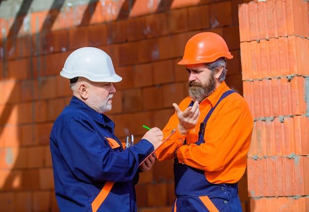 Mann mit schutzhelm arbeiter in helm zwei mechaniker auf bau werbung mechaniker baumeister in