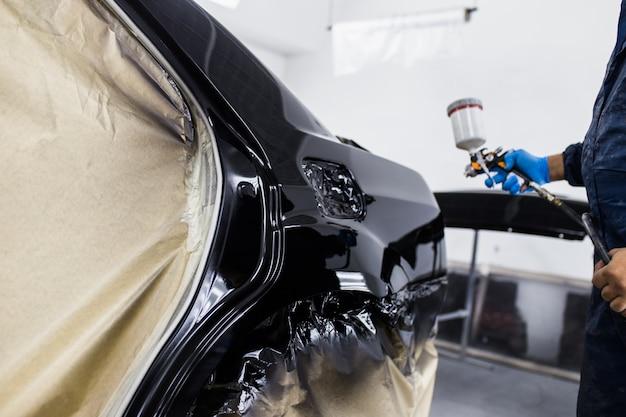 Mann mit schutzkleidung und maskenlackierung auto mit sprühkompressor. selektiver fokus.