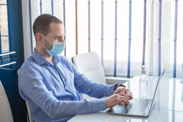 Mann mit schutzmaske, die zu hause mit laptop arbeitet.