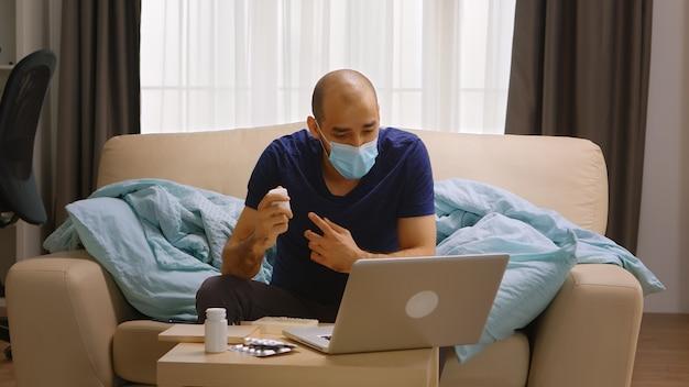 Mann mit schutzmaske während covid-19 in einem videoanruf auf dem laptop, der mit dem arzt über seine medizin spricht.