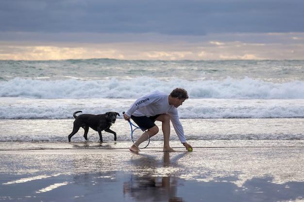 Mann mit schwarzem hund am strand von piha