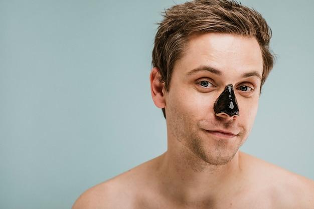 Mann mit schwarzer porenmaske