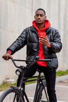 Mann mit seinem fahrrad mit seinem handy