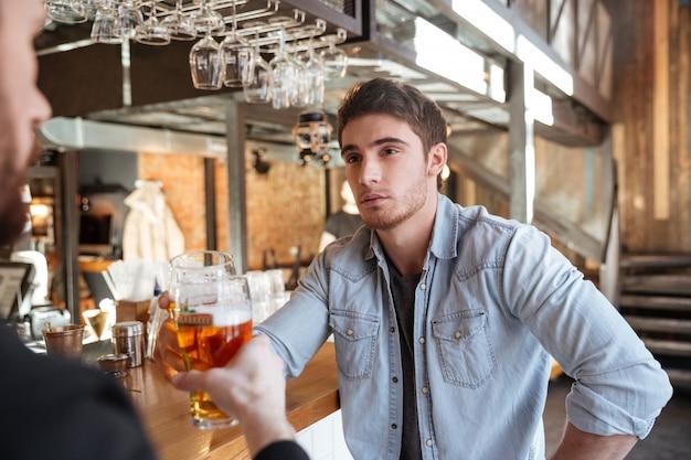 Mann mit seinem freund trinkt bier in der bar