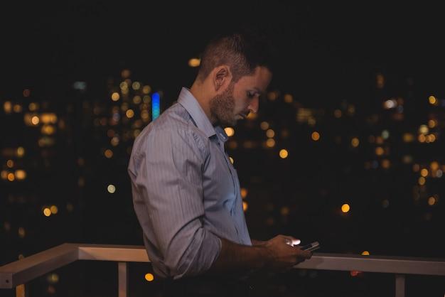 Mann mit seinem handy auf dem balkon