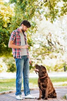 Mann mit seinem hund, der auf gehweg im garten steht
