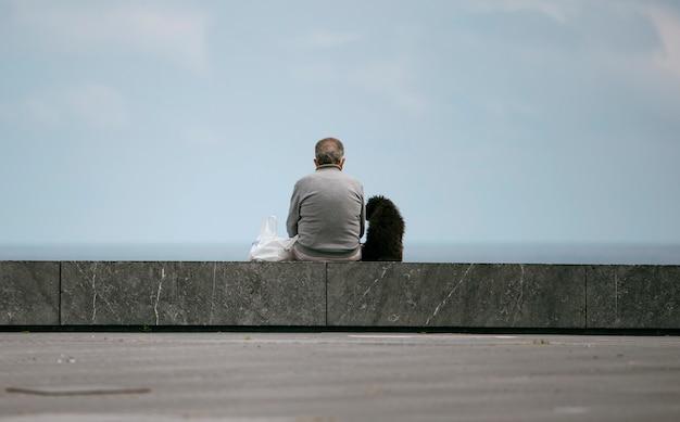 Mann mit seinem hund, der sich ausruht und auf das meer schaut