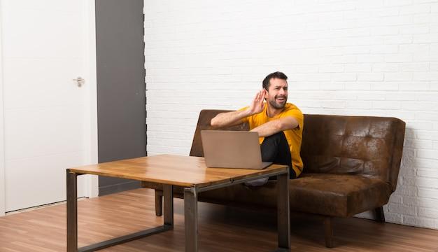 Mann mit seinem laptop in einem raum hörend auf etwas, indem er hand auf das ohr setzt