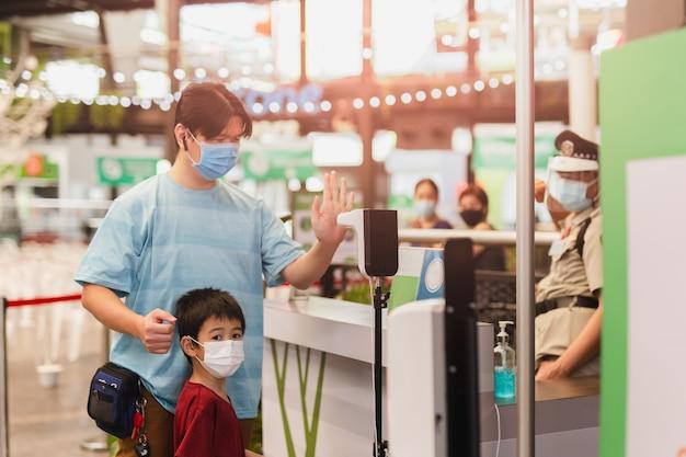 Mann mit seinem sohn, der eine medizinische maske trägt und seine hand benutzt, um seine körpertemperatur zu scannen