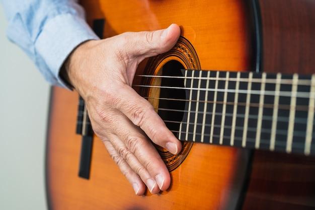 Mann mit seiner hand auf den gitarrensaiten. lernen mit einem online-kurs
