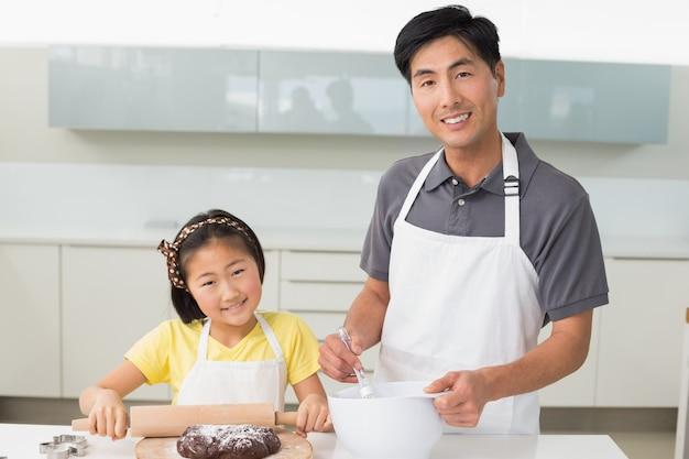 Mann mit seiner tochter, die plätzchen in der küche zubereitet
